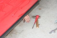 A hand appears under the car